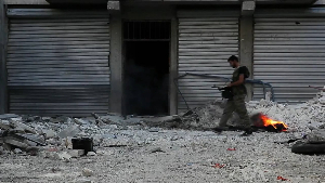 Free Syrian Army soldier walking among rubble in Aleppo